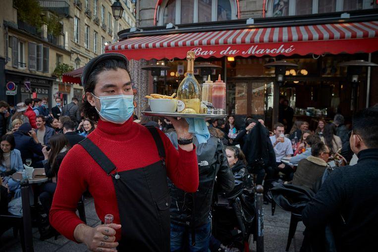 Een ober op het terras van Bar du Marche in het zesde arrondissement van Parijs.  Beeld Getty Images