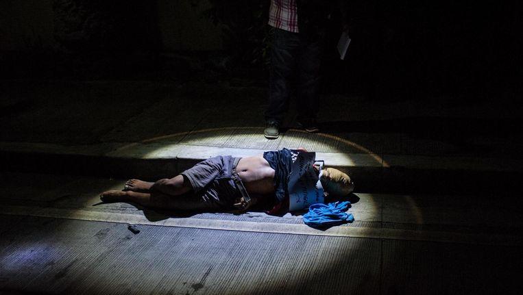 Een lijk ligt in Manilla op straat (in oktober 2016). De handen zijn op de rug gebonden en het hoofd is ingetapet Beeld Getty Images