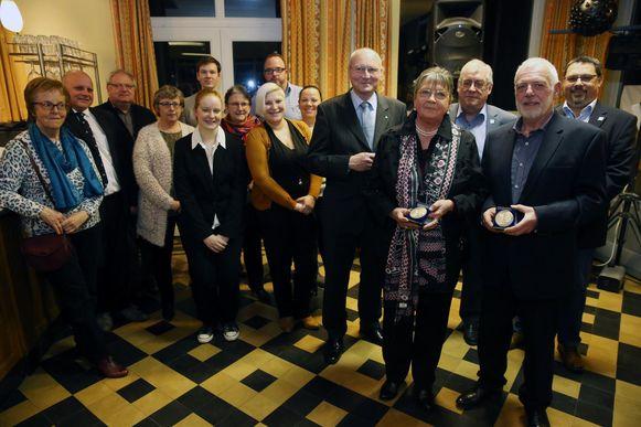 Christiane Kestemont en Elie Elsocht, beiden met gouden legpenning in de hand, en hun collega's van het Rode Kruis.