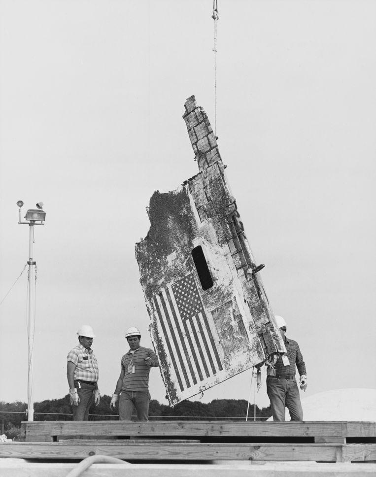 Een brokstuk van de Challenger wordt omhoog getakeld op lanceerbasis Cape Canaveral. Beeld Getty