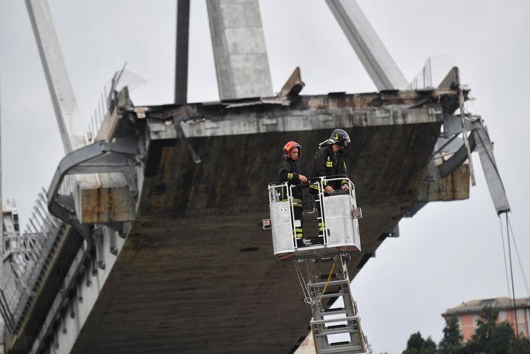 Reddingswerkers bij de rampbrug.  Beeld EPA