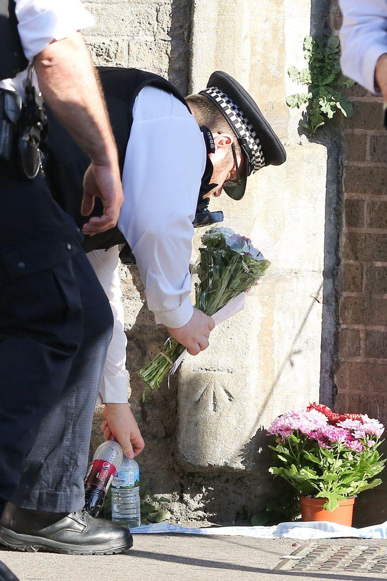 Een politieagent met bloemen bij de moskee van Finsbury Park waar deze week een man inreed op gelovigen.  Beeld Photo News