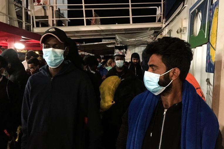 Migranten dragen beschermende mondkapje aan boord van de Ocean Viking. Beeld AFP
