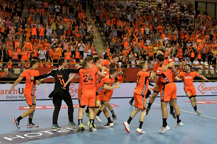 De Oranje handballers vieren feest na de zege op Letland.
