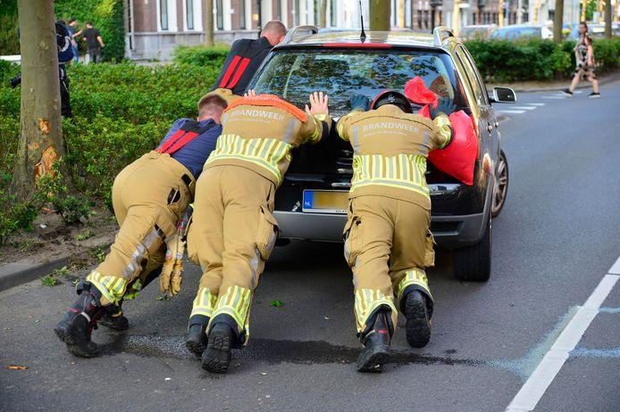 Brandweerlieden duwen de auto van de weg de stoep op