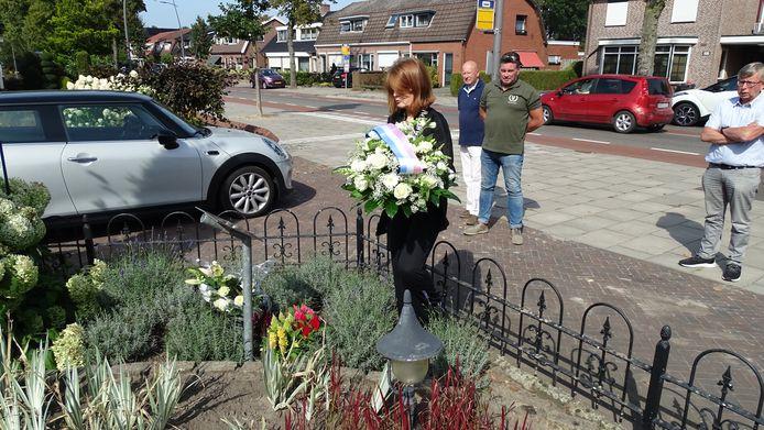 Burgemeester Cia Kroon legt bloemen bij de herinneringsplaquette van Jo ter Laak in Overdinkel