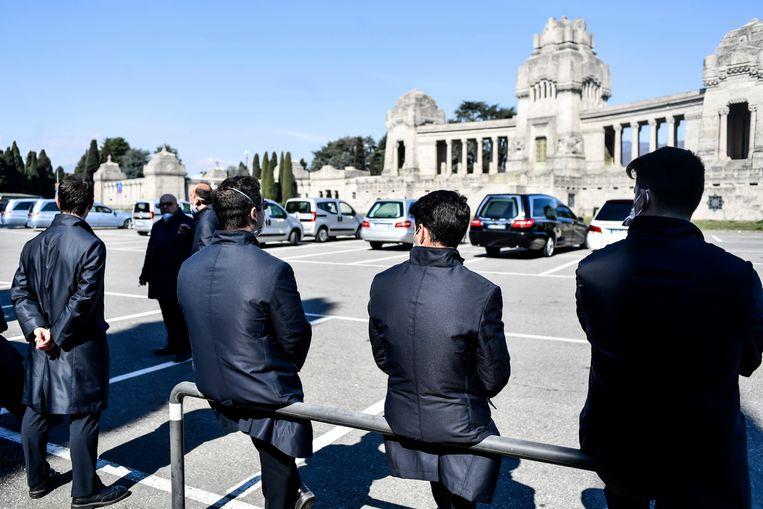 Medewerkers van het kerkhof van Bergamo waar aan de lopende band begrafenissen plaatsvinden. Beeld AP