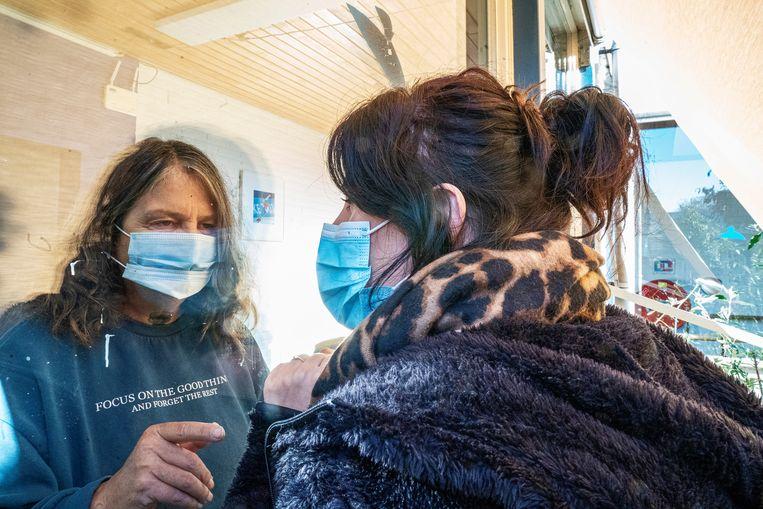 Een gesprek door het raam met een patiënt op de Covid-afdeling Beeld Inge Hondebrink