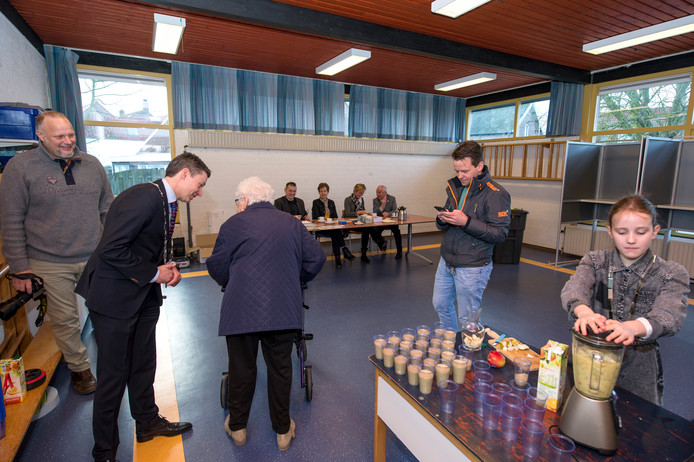 Lara van Son maakt fruitsmoothies voor vroege stemmers terwijl de burgemeester met hen praat.
