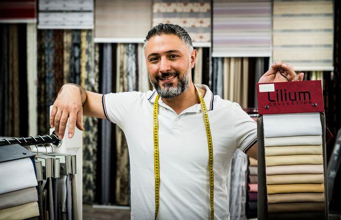 Erhan Aydin in zijn Huismode winkel met stoffen.