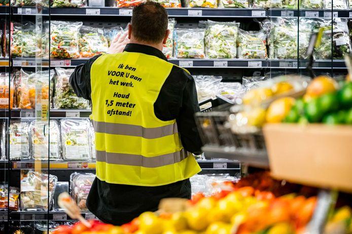 Een medewerker vult de rekken aan in een Nederlandse supermarkt, ter illustratie.