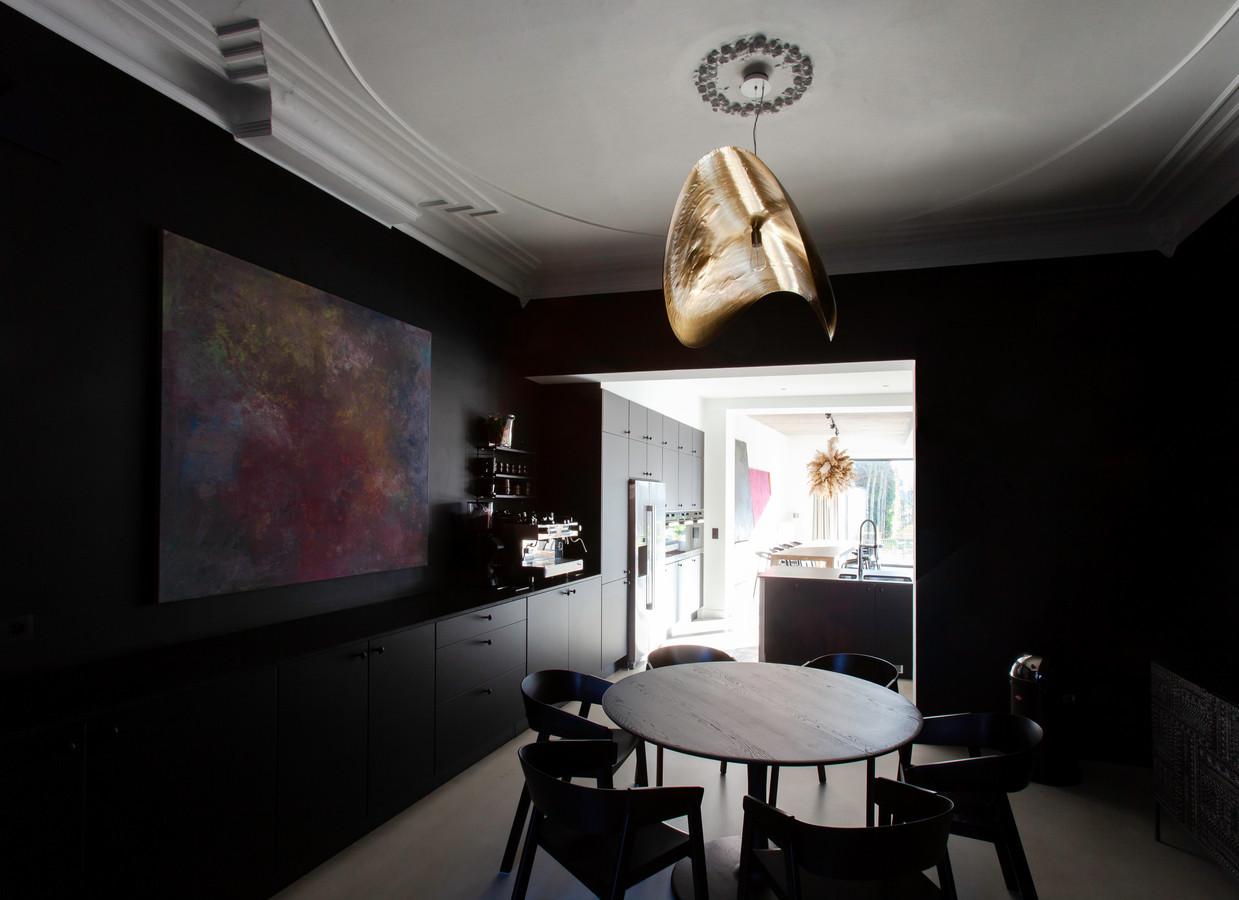 Het schilderij Confetti Island van Studio Spruyt komt goed tot zijn recht tegen de zwarte achtergrond. De lamp is van Paolo Navone.