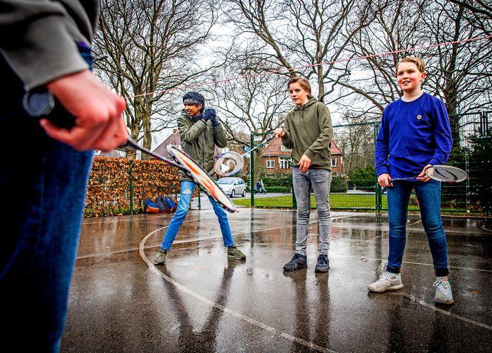 Leerlingen van het Johan de Witt-gymnasium in Dordrecht spelen buiten badminton. In het midden de 13-jarige Pascal, die vooral blij is om zijn vrienden weer te zien.