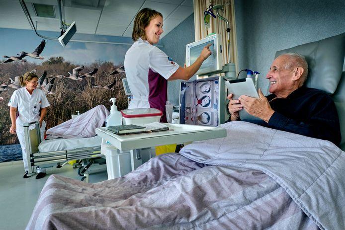 Frans Wevers (78) speelt sudoku's op zijn tablet, terwijl een dialysemachine zijn bloed schoonspoelt.
