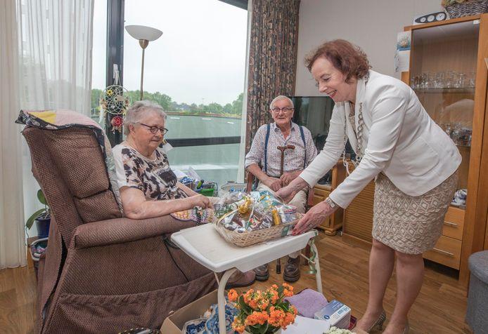 Burgemeester Loes Meeuwisse geeft een mand met Zeeuws lekkers aan Jannie Wisse-Bakker en Ko Wisse. Ze zijn 65 jaar getrouwd en Ko wordt vandaag ook nog eens 90 jaar.