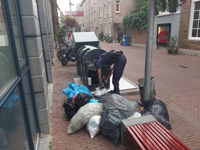 Een handhaver van de gemeente controleert in de Kerkstraat in de binnenstad van Arnhem illegaal gedumpte afvalzakken op adresgegevens. Aan de praktijk van afvaldumpingen naast containers moet een einde komen nu een meerderheid van de Arnhemmers bij het referendum heeft aangegeven dat ze weer van het slot moeten.