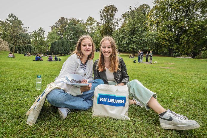 Her en der zijn de kenmerkende zakjes van de KU Leuven te spotten in het straatbeeld. Deze twee vriendinnen hebben zich al neergevlijd in het stadspark, een hotspot voor studenten, zeker als het zonnetje schijnt.