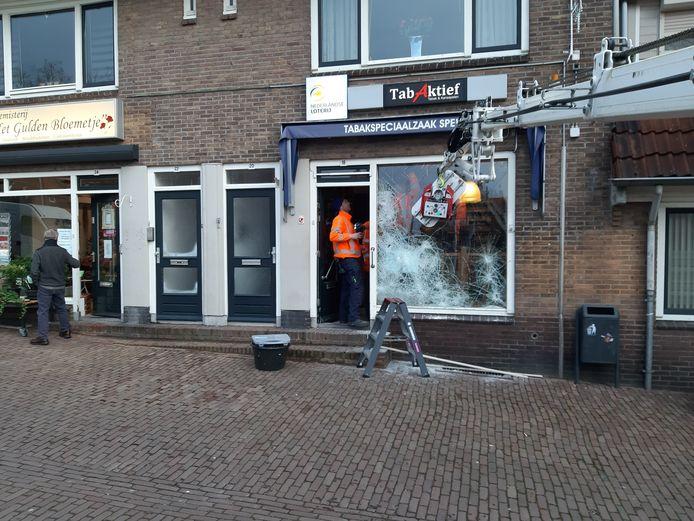Glaszetters zijn in de weer met de etalageruit van de tabakszaak op de Geitenkamp in Arnhem, die vernield werd bij een inbraak.