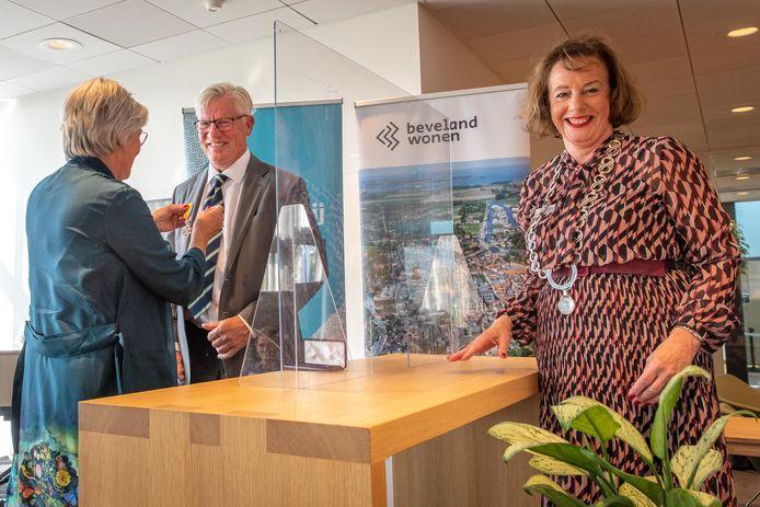 Maarten Sas krijgt zijn onderscheiding opgespeld door zijn vrouw. Rechts burgemeester Loes Meeuwisse van Noord-Beveland achter het corona-spatscherm.