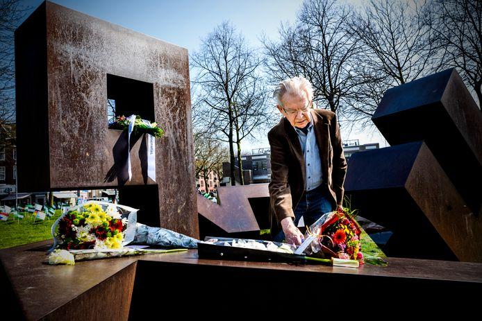 Ooggetuige Bob Briegoos legt een bloemetje bij het monument in Park 1943. 'Het is heel belangrijk om hier te blijven komen'.