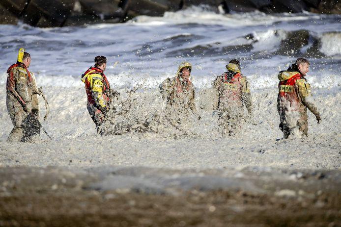 Leden van de KNRM ploegen door het schuim in de zoektocht naar de vermiste watersporters bij het noordelijk havenhoofd.