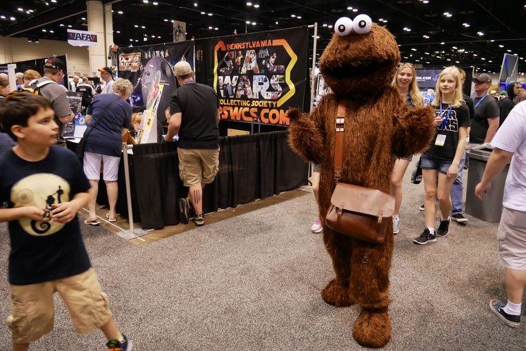 """Wie? Robert (46), heeft een winkel met Biker Jewelry, woont in Daytona Beach (Florida) •  Waarom? """"Dit is mijn tweede Celebration en mocht ik het kunnen betalen zou ik elk jaar terugkomen. Deze keer heb ik voor het eerst een kostuum in elkaar gestoken. Als kind was ik gek van Star Wars én Sesamstraat. Dus heb ik hier mijn favoriete personages samengebracht: Chewbacca en Cookie Monster. Iedereen lijkt het leuk te vinden."""" •  Hoeveel? """"Waarschijnlijk zo'n 2.000 dollar."""" Beeld Robin Broos"""