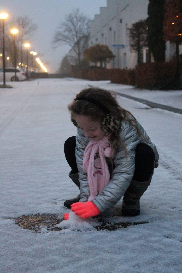Annemiek uit Teteringen kan nog snel een foto maken van haar dochter, voor ze zal moeten bukken voor de sneeuwbal.