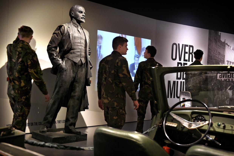 Militairen bekijken de tentoonstelling, waar ook een beeld van Lenin staat. Beeld Marcel van den Bergh / de Volkskrant