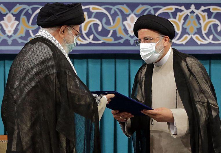Ayatollah Ali Khamenei (L) en de nieuwe president Ebrahim Raisi (R) in de Iraanse hoofdstad Teheran. Beeld AFP