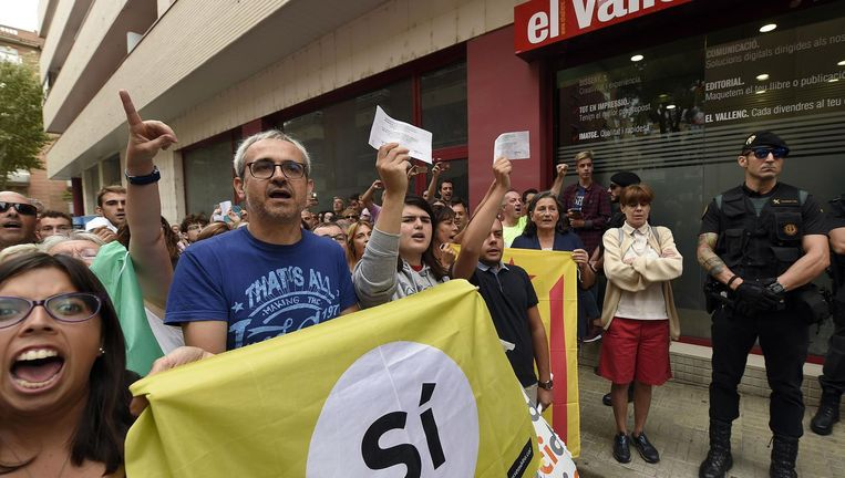 Voorstanders van het referendum over Catalaanse afscheiding demonstreren bij de krant El Valenc, waar de Spaanse Guardia Civil zaterdag een inval heeft gedaan. Beeld AFP