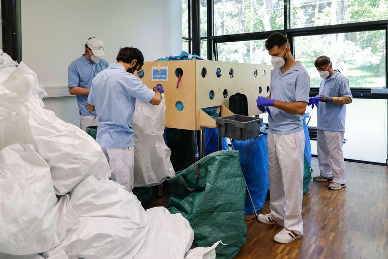 Zorgmedewerkers pakken een lading PCR-tests uit, à 149 euro per stuk. Beeld AP