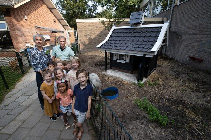 Leerkrachten Jan Coumans (l) en Rob Meeusen met kinderen bij Spekkie, het nieuwe dierenverblijf.