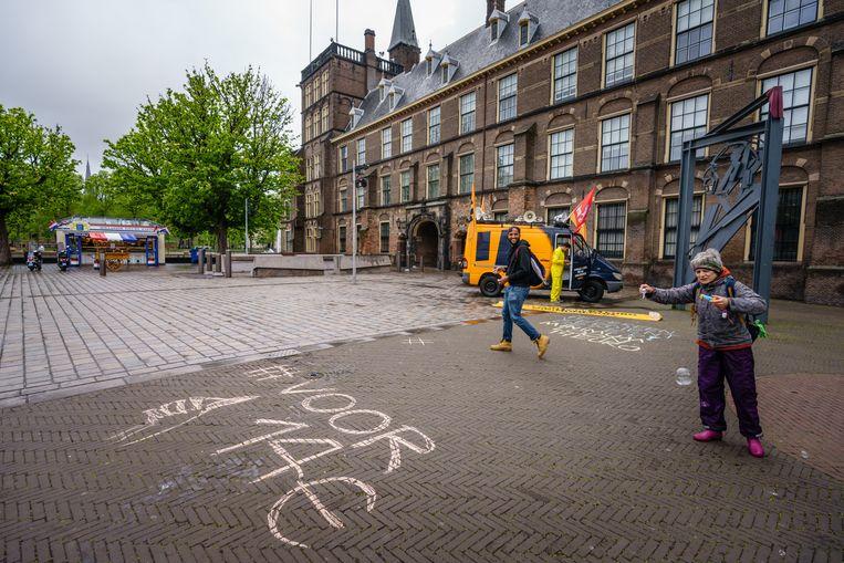 Krijten voor 14! Bij het monument van Willem Drees op de Hofplaats krijten actievoerders de eis van een minimumuurloon van 14 euro op de stoep. Beeld Martijn Beekman