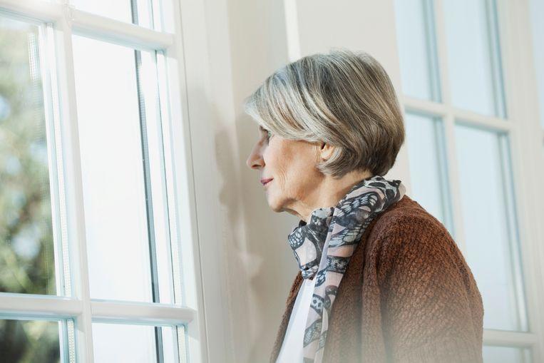 Vrouw kijkt uit raam Beeld Getty Images/Westend61