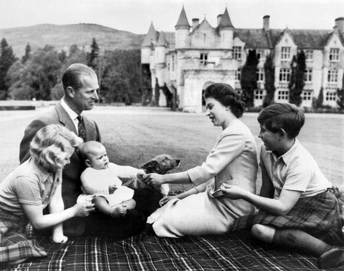 9 september 1960. Queen Elizabeth, prins Philip en hun drie kinderen prins Charles (R), prinses Anne (L) en prins Andrew (baby) in de tuin van het Balmoral-landgoed. Op de achtergrond het sprookjesachtige Balmoral-kasteel.