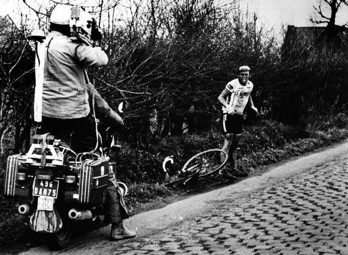 Hennie Kuiper staat langs de kant van de weg, wachtend op een nieuwe fiets, met zijn kapotte fiets naast hem in Parijs-Roubaix 1983.