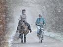 Daphne de Visser en zus Esmée (op fiets) maken bij Aagtekerke een ritje door de sneeuwbui.