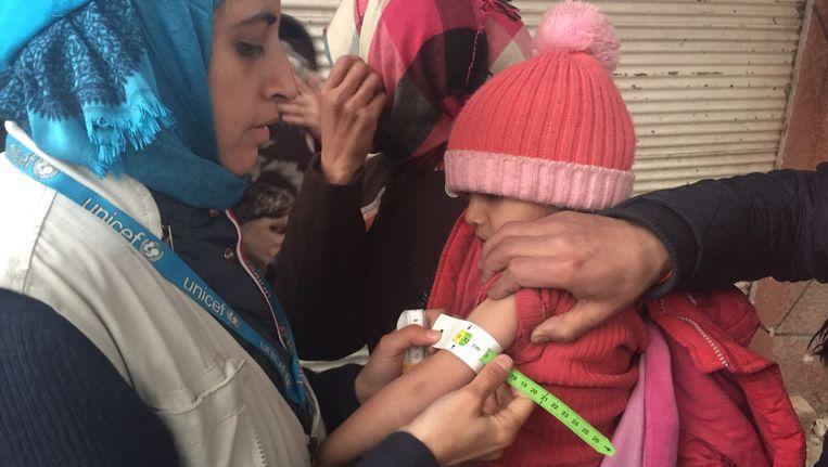 Een medewerker van UNICEF meet de arm van een ondervoed kind in de Syrische stad Madaya. (archieffoto januari 22016). Beeld AFP