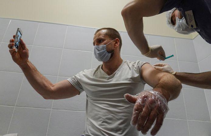 Een man maakt in Moskou een selfie van het moment waarop hij het Spoetnik-vaccin krijgt toegediend.
