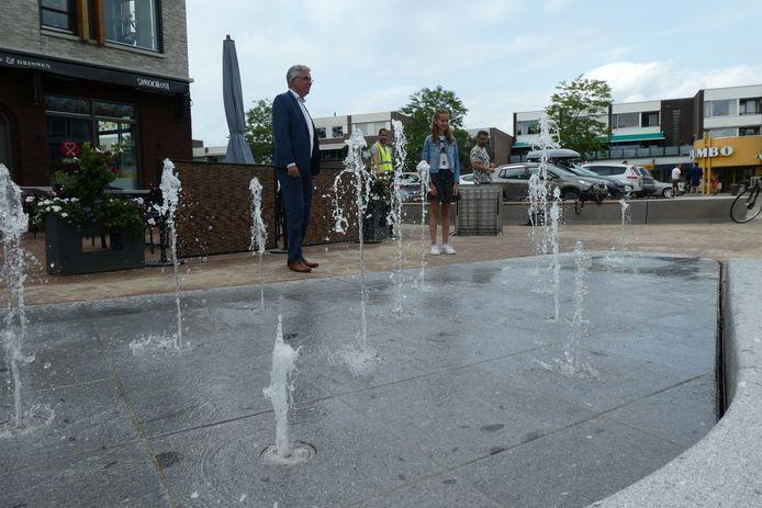 De nieuwe fontein is in gebruik op het Mercuriusplein. Madelif Houtman (kinderburgemeester) en wethouder Mathijssen zetten de kraan aan.