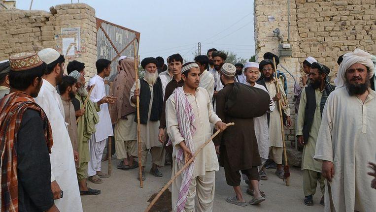 Pakistaanse moslims staan voor een verwoeste winkel in de stad Peshawar. Beeld afp
