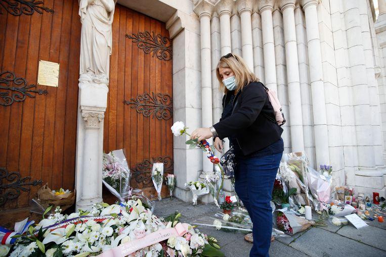 Een vrouw bij de ingang van de kerk in Nice, waar donderdag drie mensen zijn neergestoken.  Beeld EPA