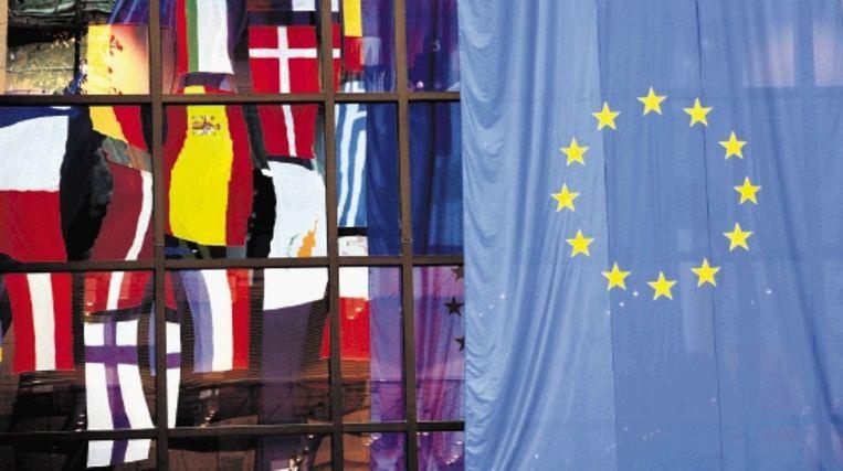 De vlag met het EU-logo tooit samen met de vlaggen van de EU-lidstaten het gebouw van de Europese Commissie in Brussel. (EPA) Beeld EPA