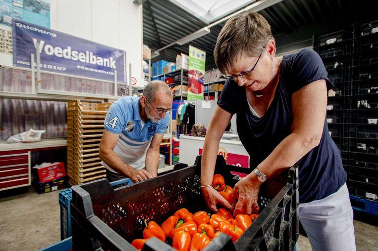 Vrijwilligers sorteren kilo's paprika's bij de voedselbank in Maassluis. Beeld ANP