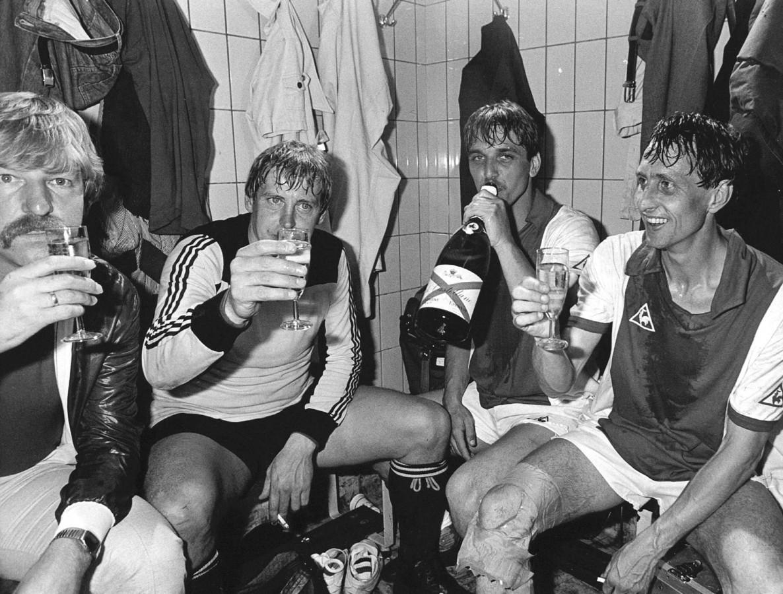 Johan Cruijff (r) viert het behalen van de landstitel met Ajax na een 3-2 zege op AZ. Aad de Mos, Piet Schrijvers en Edo Ophof (vlnr) heffen het glas met de grootmeester.