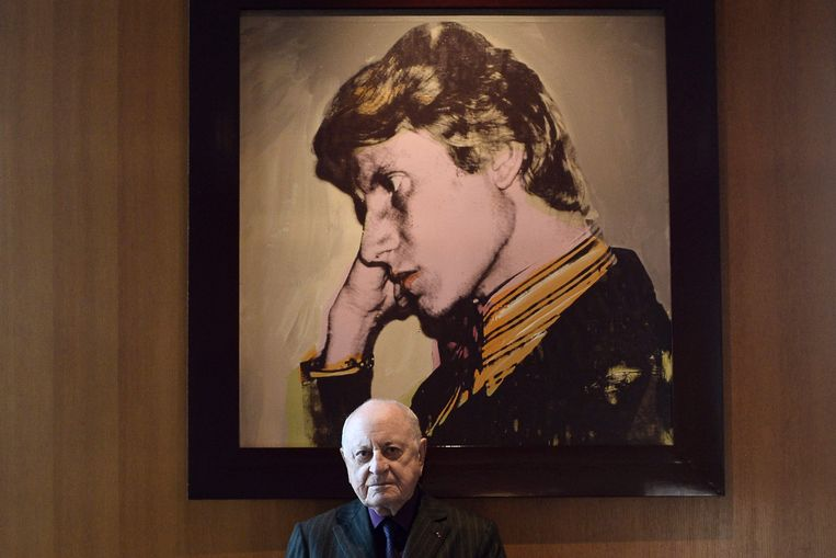 Pierre Bergé voor een portret van Yves Saint Laurent door Andy Warhol in 2015. Beeld AFP