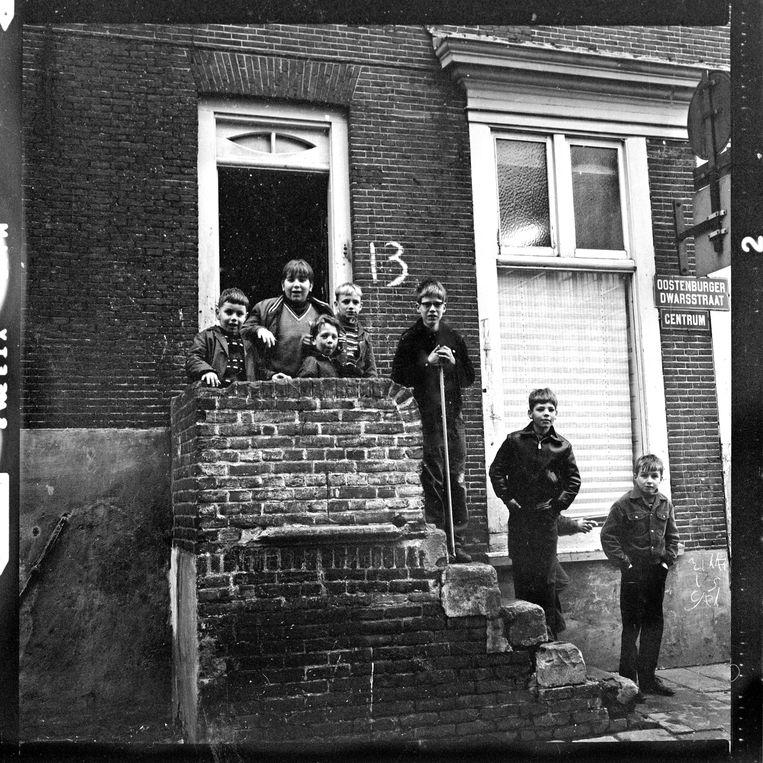 Oostenburg, 1967. De Oostenburgerdwarsstraat in het centrum. Jongensbende poseert op de trap voor hun portiek op nr. 13. Op de muur graffitti Rikki is gek. Beeld bert verhoeff