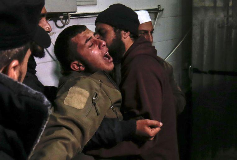 Een familielid van de 24-jarige Mohammed al-Nabaheen, die door Israëlische tanks dodelijk geraakt werd, huilt bij het vernemen van de dood van de jonge man. Beeld AFP