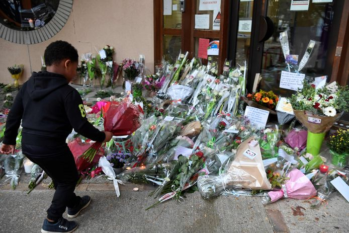 A child lays flowers at the entrance of a middle school in Conflans-Sainte-Honorine, 30kms northwest of Paris, on October 17, 2020, after a teacher was decapitated by an attacker who has been shot dead by policemen. - The man suspected of beheading on October 16 ,2020 a French teacher who had shown his students cartoons of the prophet Mohammed was an 18-year-old born in Moscow and originating from Russia's southern region of Chechnya, a judicial source said on October 17. Five more people have been detained over the murder on October 16 ,2020 outside Paris, including the parents of a child at the school where the teacher was working, bringing to nine the total number currently under arrest, said the source, who asked not to be named. The attack happened at around 5 pm (1500 GMT) near a school in Conflans-Sainte-Honorine, a western suburb of the French capital. The man who was decapitated was a history teacher who had recently shown caricatures of the Prophet Mohammed in class. (Photo by Bertrand GUAY / AFP)