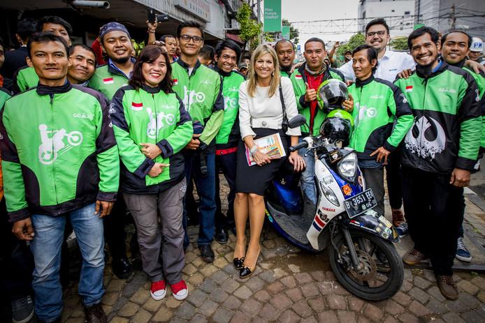 Koningin Maxima tijdens een bezoek aan Indonesië poseert met medewerkers van Go-Jek, een telefonische scooterdienst die verschillende diensten aanbied zoals maaltijden, transport en andere logistieke diensten. Foto Patrick van Katwijk